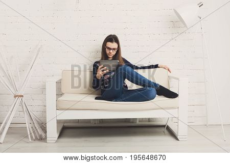 Teenage girl in eye glasses look into tablet, sitting on sofa. Children computer games, social networks and media addiction concept. Communication technologies, copy space