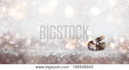 Abstract silver glitter bokeh background with wedding rings for a invitation