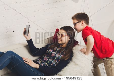 Group of kids in eye glasses look into tablet. Children computer games, social networks and media addiction concept. Girl and boys with gadget. Communication technologies.