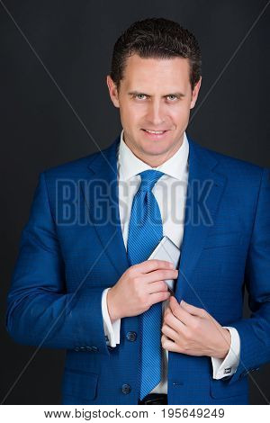 Businessman happy man or smiling manager hiding smartphone or mobile phone in blue suit with tie on black background. Technology for business. Digital marketing internet surfing and information