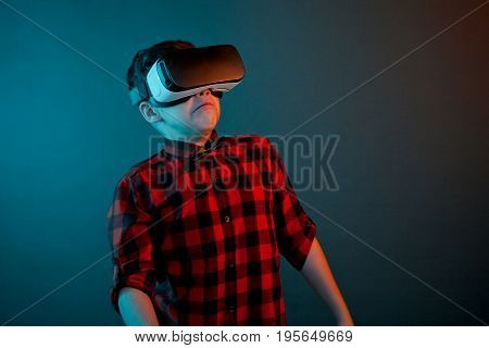 Casual boy wearing VR goggles and looking terrified on dark background.