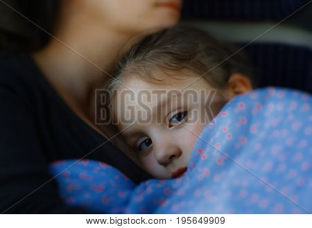 Little girl trying to sleep in her mother's arms