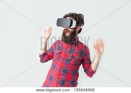 Man with hands up having a virtual reality experience. Horizontal studio shot.