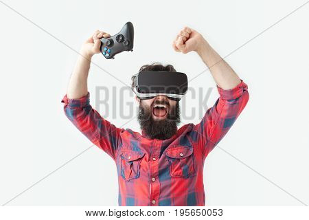 Bearded expressive man in VR goggles winning the game and holding hands with gamepad up.