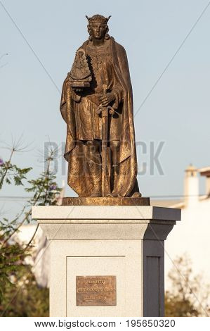 Almonte Spain - June 3 2017: Bronze statue of a pilgrim holding a figure of Madonna of El Rocio. Almonte Andalusia Spain