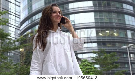 Happy satisfied businesswoman in white shirt talking on phone.