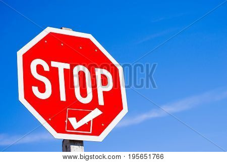 Stop sign with checed box concept of stop and check first against blue sky background