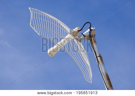 A wireless internet reciever dish for home and business use with blue sky as background