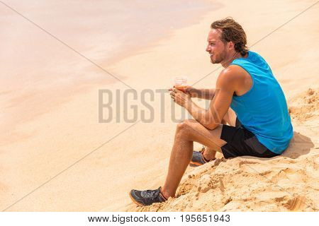 Healthy fitness man drinking detox juice drink on beach run. Runner athlete relaxing on training break with juice smoothie for diet.