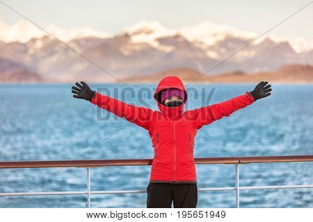 Alaska Glacier bay cruise travel fun tourist excited looking at inside passage. Happy woman with open arms in joy of seeing Alaskan nature landscape in the USA.