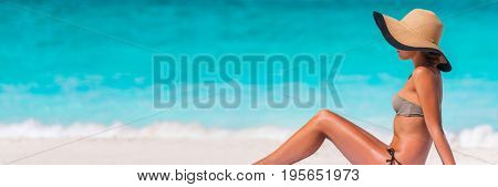 Beach vacation bikini woman relaxing banner with blue water texture copyspace background. Travel holiday panorama concept, girl sunbathing with sun hat lying down on sand. Tropical holidays.
