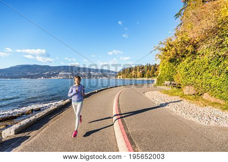 Runner girl running in Stanley Park Vancouver, British Columbia. Woman jogging in city outdoors enjoying healthy active lifestyle.