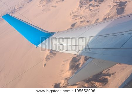 Airplane wing blue and white plane flying above rugged hilly desert adventure travel summer vacation concept