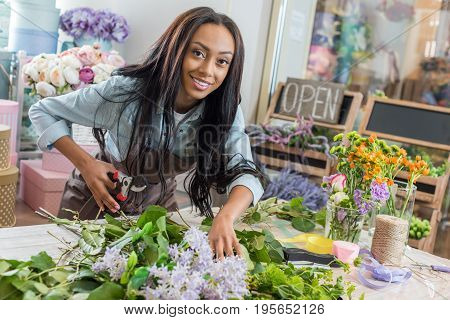 Beautiful African American Woman In Apron Holding Secateurs While Cutting Flowers And Smiling At Cam