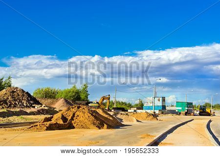 Mountains of white sand lie on side of road. Construction of high-speed ring road around Krasnoe Selo Saint Petersburg. Civil and industrial construction. Russia