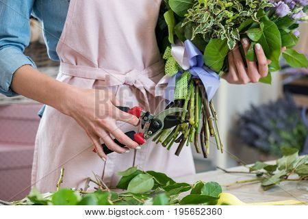 Cropped Shot Of Young Florist In Apron Holding Bouquet And Cutting Green Stems With Secateurs