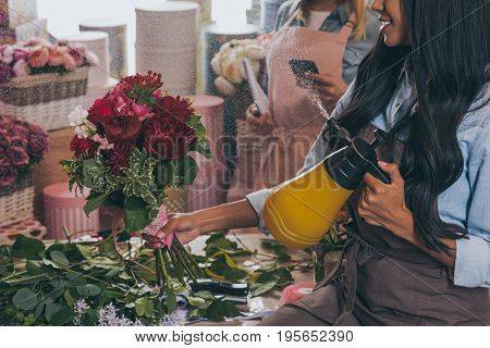 Cropped Shot Of Smiling African American Florist Watering Bouquet Of Beautiful Flowers