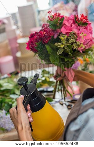 Cropped Shot Of Florist Watering Bouquet Of Beautiful Flowers