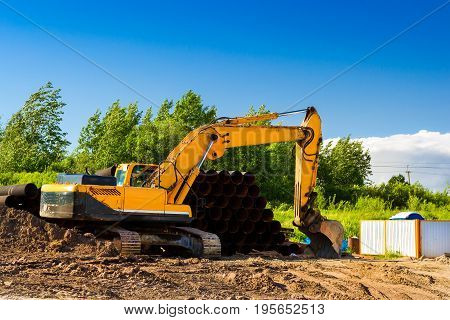Crawler Excavator digging bucket on construction of high-speed ring road around Krasnoe Selo Saint Petersburg. Heavy machine equipment for excavation works at civil industrial construction. Russia