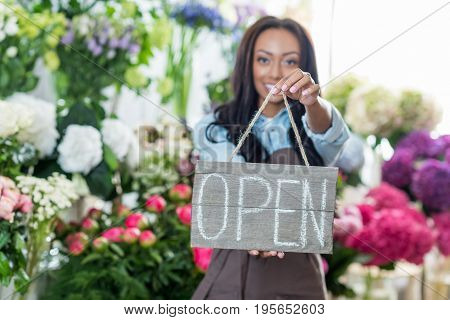 Beautiful African American Florist Holding Open Sign And Smiling At Camera