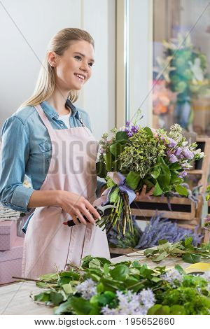 Young Smiling Blonde Florist Holding Bouquet And Cutting Green Stems With Secateurs