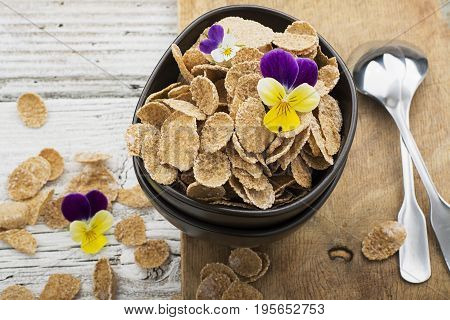 The concept of a healthy breakfast: whole-grain flakes with edible garden flowers, berries in dark ceramic bowls on a light wooden background. Selective focus