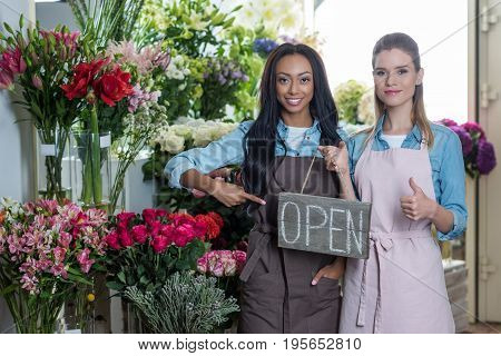 Young Multiethnic Florists Pointing At Open Sign And Showing Thumb Up While Smiling At Camera In Flo