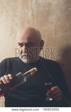 Man pouring wine to glass from bottle. Senior person or pensioner with grey beard in black sweater on beige. Alcohol and appetizer. Unhealthy lifestyle and bad habits
