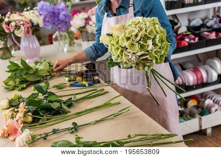Cropped Shot Of Young Florist In Apron Working With Flowers And Arranging Bouquet