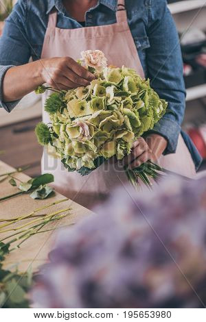 Cropped Shot Of Young Florist In Apron Holding Beautiful Bouquet While Arranging Flowers