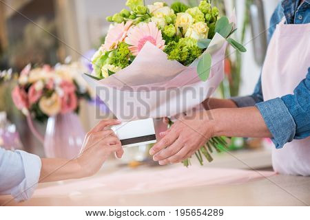 Cropped Shot Of Client Giving Credit Card To Florist Holding Bouquet