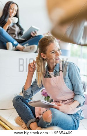 Smiling Blonde Woman Holding Notebook And Looking Away While Colleague Drinking Coffee And Using Dig