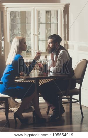 Woman and man dating in restaurant. Girl with blond hair and hipster drinking wine from martini glasses. Couple in love. Alcohol and appetizer. Addictive and convive. Unhealthy lifestyle. Bad habits