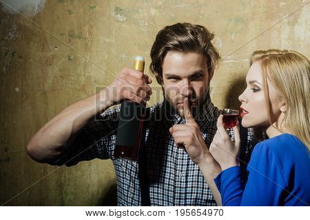Man With Bottle Making Silence Gesture And Woman Drinking