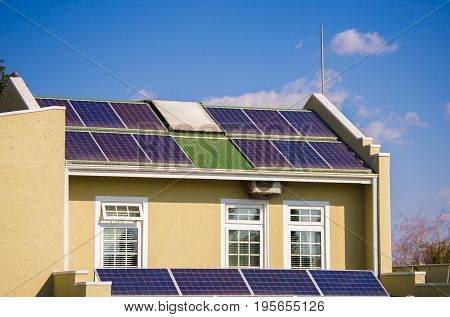 Unique solar panel installation with two levels of solar panel rows on a roof of a house against blue sky and clouds