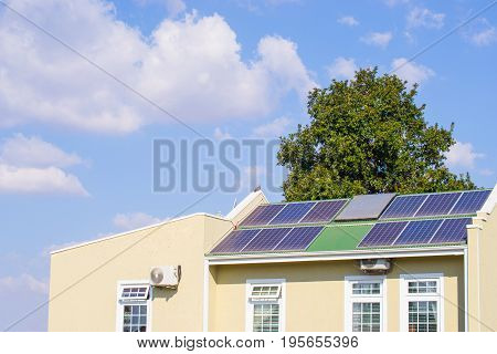 Solar panels on a roof of a house generating renweable energy with a green tree behind the house with blue sky and clouds
