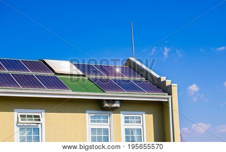 House making use of renewable enrgy with solar panels installed on the roof on a sunny day against a blue sky with clouds