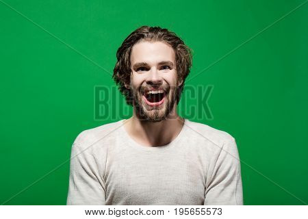 happy man with wet head face and long hair refreshing in morning in underwear on green background