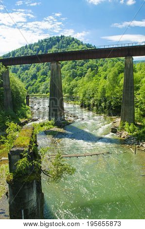 Mountain river with fast flow of clean water and the old bridge