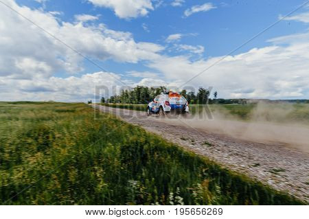 Filimonovo Russia - July 10 2017: rally car driving on a dust road in green grass and blue sky during Silk way rally
