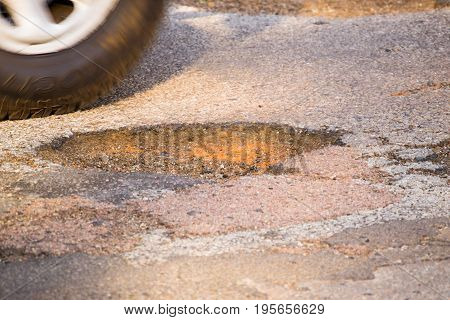 Moving car wheel on tar road avoiding a pothole