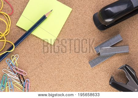 Background image with note paper, staples and a stapler on a cork board with copy space