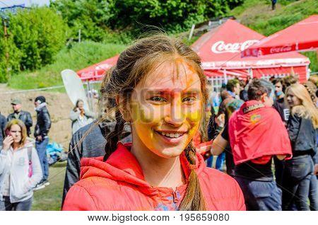Moscow, Russia - June 3, 2017: Portrait of a teenage girl surrounded by red color at the Holi Color Festival. Traditional summer Indian festival Holi turned into a fun event in many countries of world