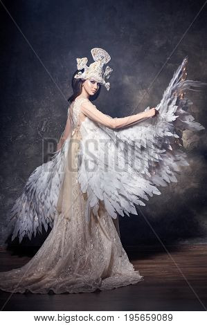 Art angel girl with wings fairy image. Swan Princess Queen of angels. Lovely dress with wings. Studio beauty portrait