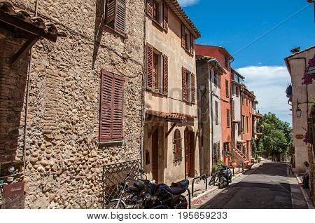 Haut-de-Cagnes, France - July 14, 2016. View of alleyway with houses on the slope and blue sky in Haut-de-Cagnes, a pleasant village on top of a hill. Alpes-Maritimes department, Provence region