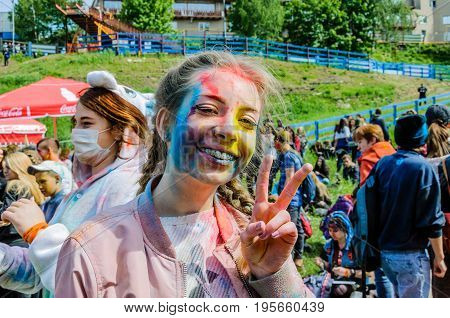 Moscow, Russia - June 3, 2017: A teenage girl with braces and pigtails, greased with multicolored paint, smiles broadly and shows a gesture of victory with her fingers at the Holi Color Festival