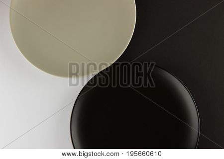 A number of flat plates and square-shaped cups on black and white background