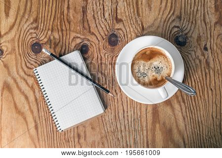 Blank notepad pencil and coffee cup on vintage wooden table background. Template for placing your design
