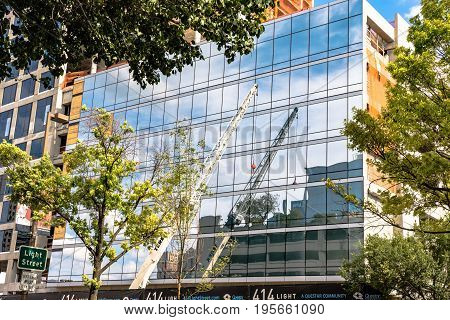 Baltimore Maryland USA - July 8 2017: Terex construction crane reflected on a building on Light Street in Baltimore Maryland.