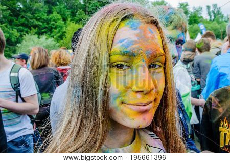 Moscow, Russia - June 3, 2017: Portrait of teenage girl at festival of colours Holi, face stained with colorful paint closeup. Summer celebration Holi turned into fun event in many countries of world